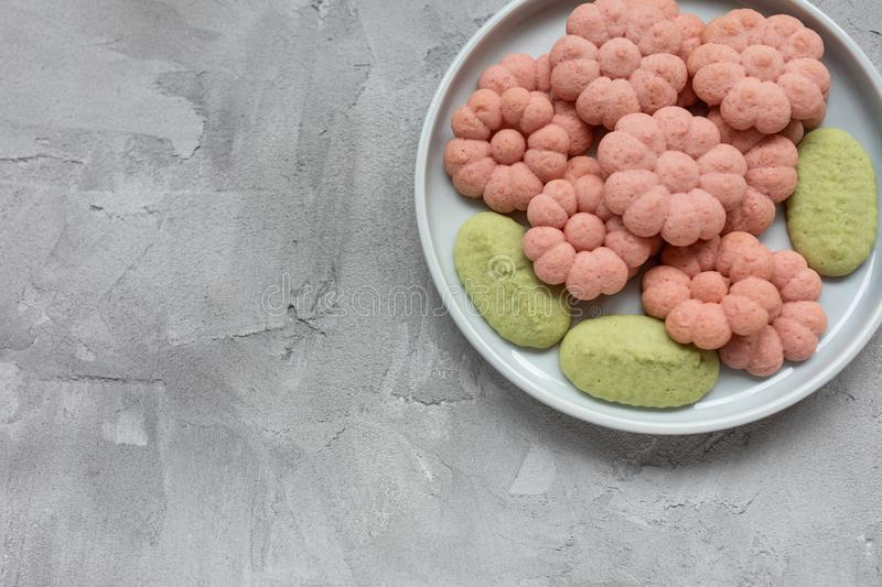 Flower cookies on a plate on a gray background . Spring holidays cooking concept. Top view, flat lay, copy space royalty free stock images