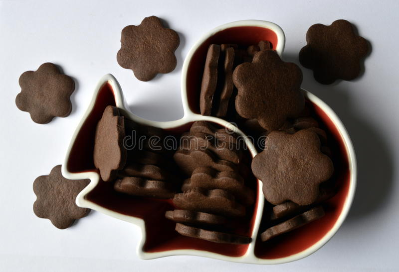 Flower cookies. Stack of homemade dark chocolate flower shaped cookies in squirrel plate stock photography