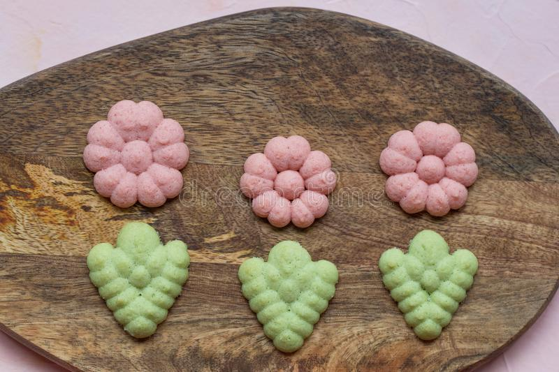 Flower cookies on a wooden board on a pink background . Spring holidays cooking concept. Top view, flat lay stock photography