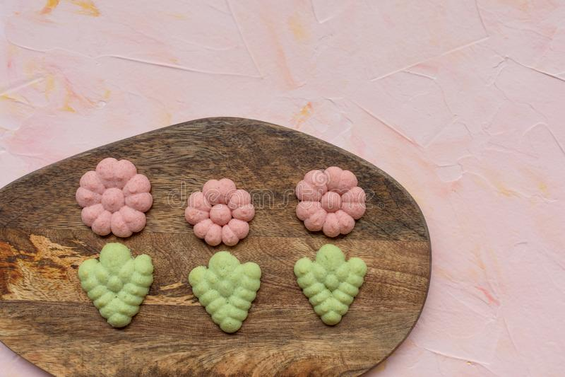 Flower cookies on a wooden board on a pink background . Spring holidays cooking concept. Top view, flat lay, copy space royalty free stock photography