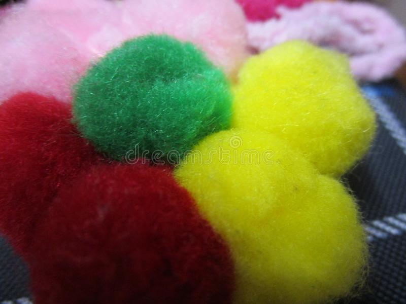 Flower craft made of green, red, yellow and pink pompoms close up stock images