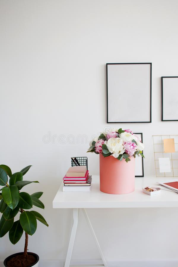Flower delivery to office. Working space, table with notebooks and magazines. Luxurious bouquet of peonies in pink box. royalty free stock image