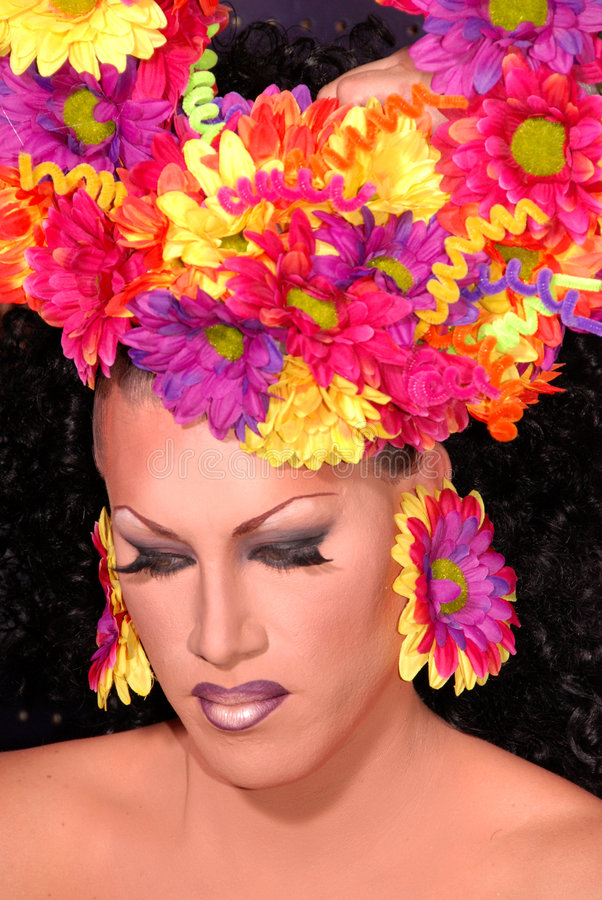 Flower Drag queen. Drag queen wearing a colorful flower head piece, and earrings royalty free stock photo
