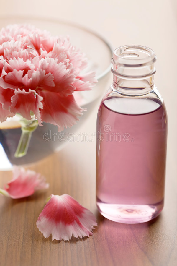 Flower and essential oil in bottle stock images