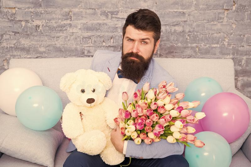 The flower experts. Spring gift. Bearded man hipster with flowers. Bearded man with tulip bouquet. March 8. Love date royalty free stock photos