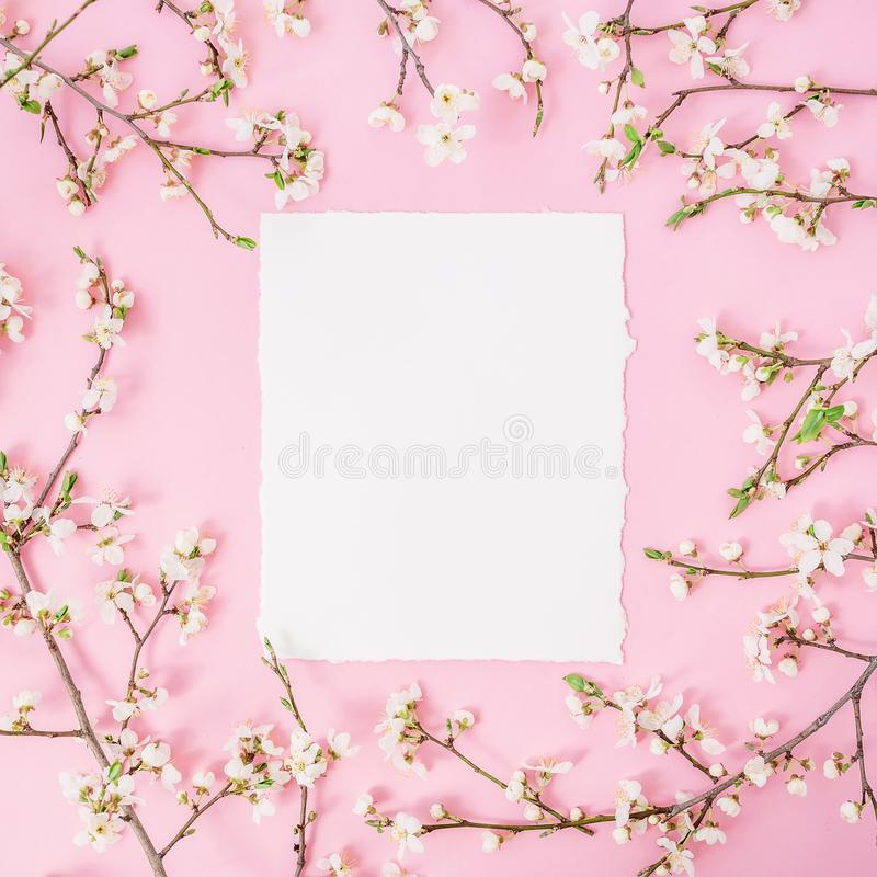 Flower frame with white flowers and paper vintage card on pink background. Flat lay, top view. royalty free stock photos