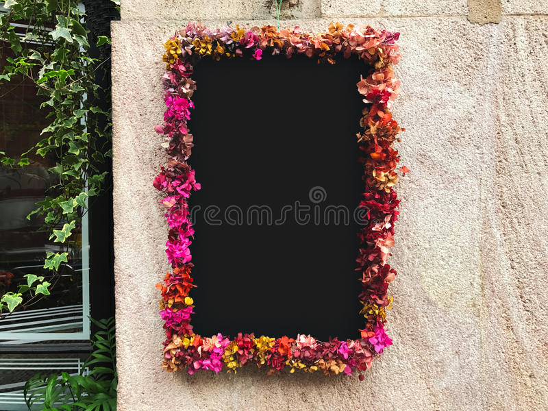 Flower framed around chalkboard on stone wall royalty free stock photo