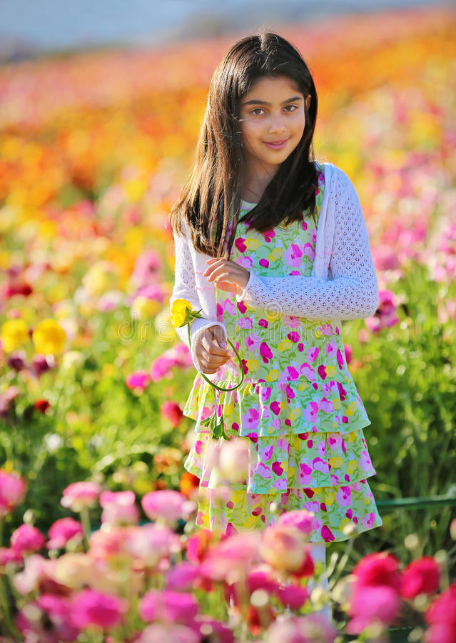 Flower garden. Girl dressed in floral enjoying a walk in a flower garden stock image
