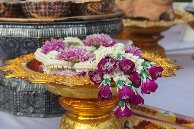 Flower Garland on Gold Tray. Flower Garland on a gold tray. Decoration by using purple flowers and jasmines. Thai people usually use flower garland to worship or stock photos