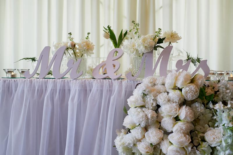 Flower garland of pine-shaped roses hangs from the table. Wedding decoration,floristry stock photography