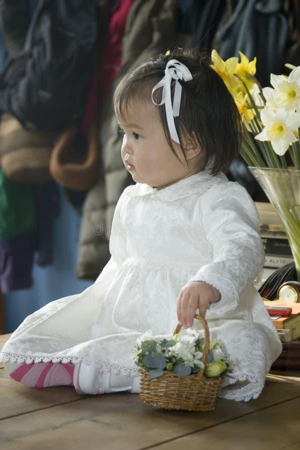 Flower girl. Asian flower girl in pretty white dress royalty free stock image