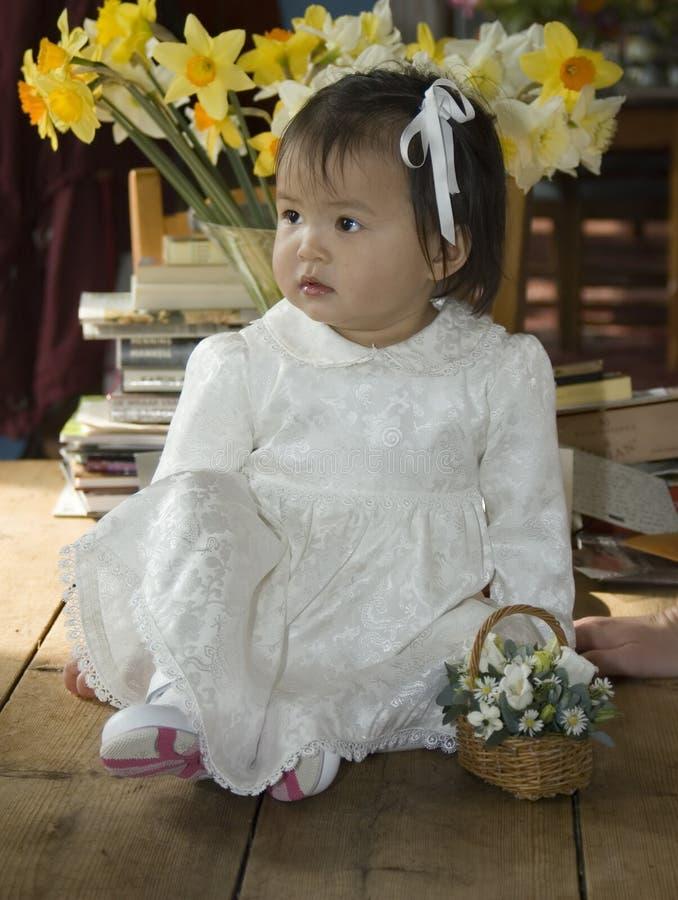 Flower girl. Asian flower girl in pretty white dress royalty free stock photography