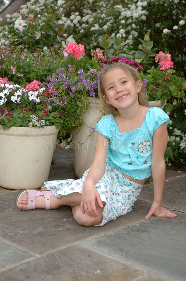 Flower Girl. Little girl sits on the ground in front of beautiful flowers stock photo