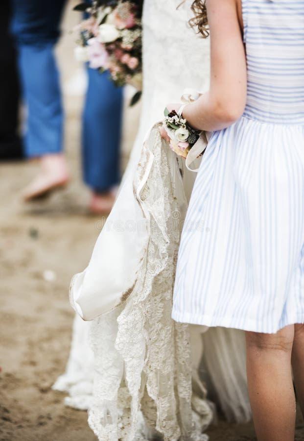 Flower girl holding bridal wedding dress stock photography