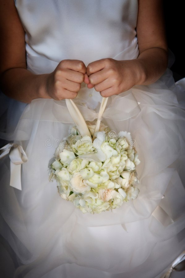 Flower girl holding her bouquet. An image of a flower girl holding her bouquet royalty free stock photo