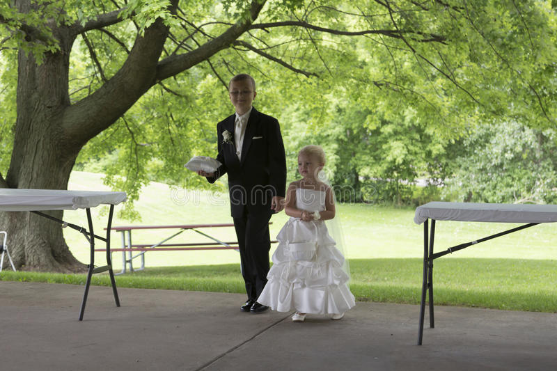 Flower Girl and Ring Bearer. Young ringer bearer dressed in his best escorts a younger flower girl down the isle stock image