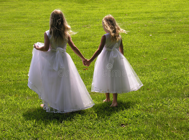 Flower girls holding hands. Two flower girls walk across the grass holding hands royalty free stock photos