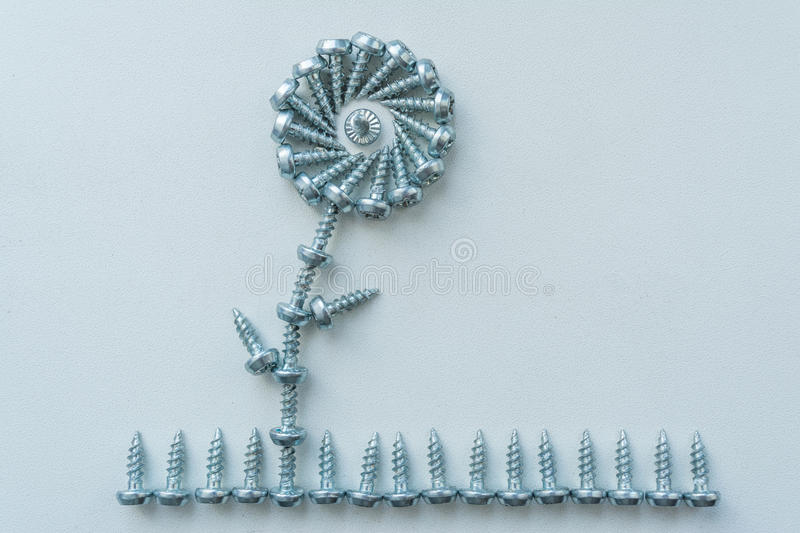 Flower on grass. Abstract composition of screws stock image