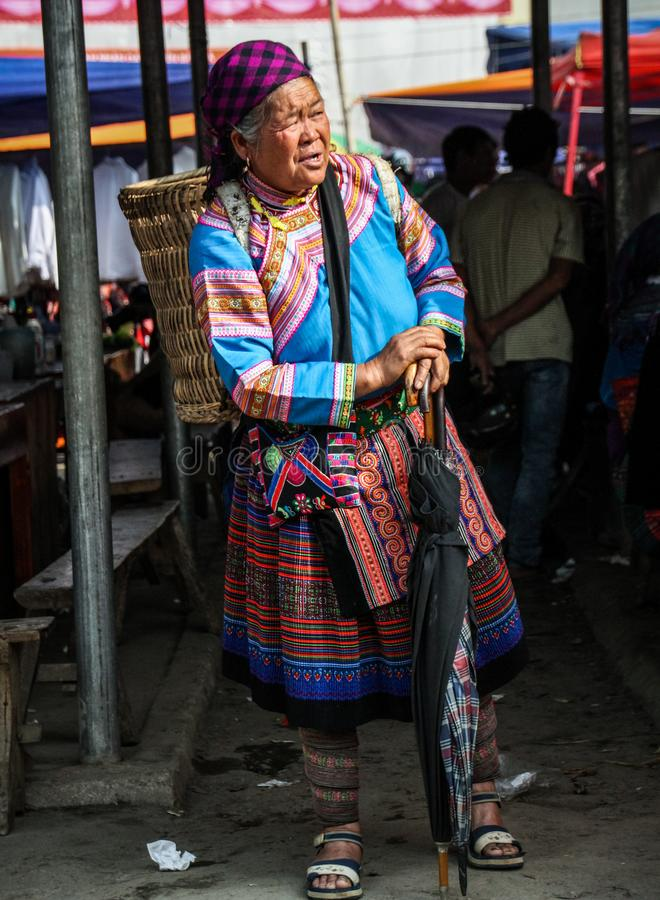 Flower hmong woman waiting for a transport at the Bac Ha Market, Lao Cai, Vietnam royalty free stock image