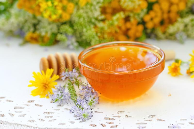Flower honey in glass bowl. Honey in glass bowl with flowers background stock photos