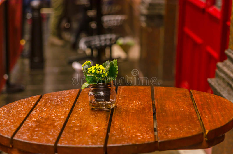 Flower in a jar on the restaurant table after rain. Wet table stock photos