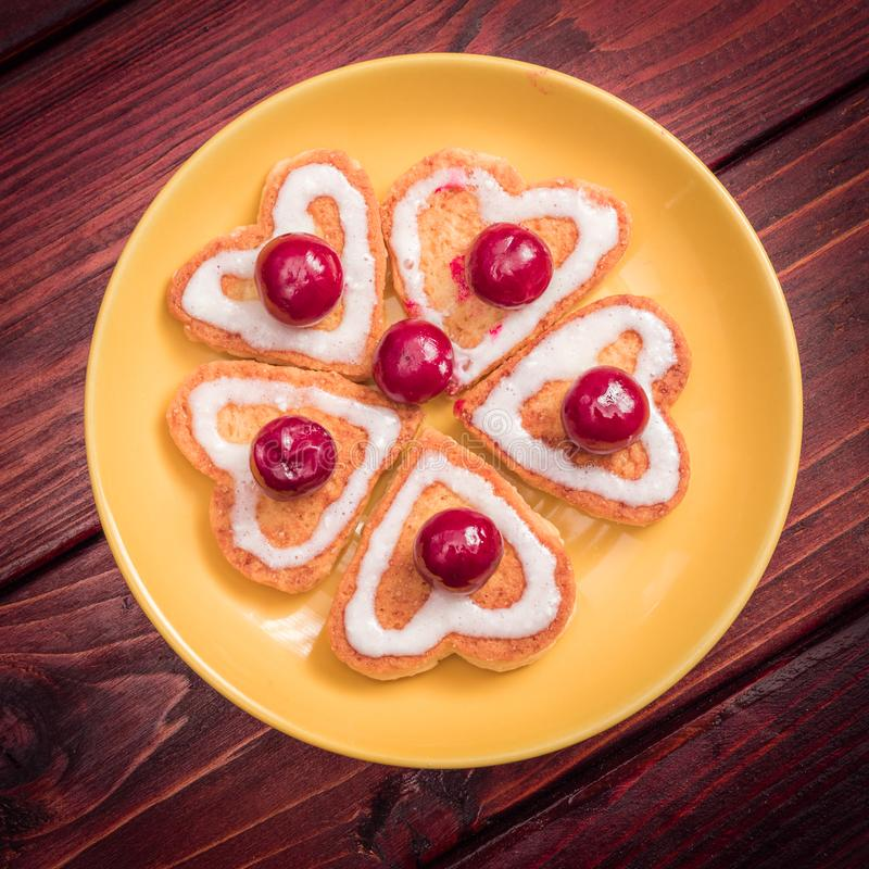 A flower laid out of heart-shaped cookies with frozen cherries on top. Valentines day stock images