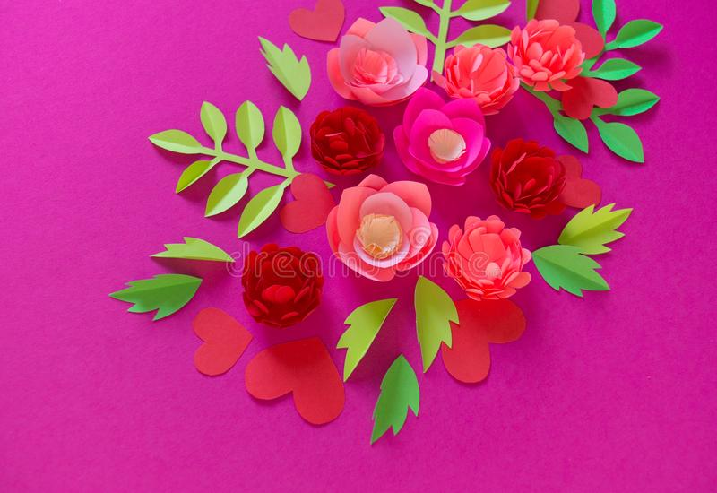 Flower made of paper pink background. Trend color pastel coral. Handwork is a favorite hobby. Florist salon advertising. Green tropical leaf and curl stock photos