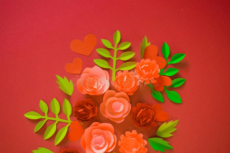Flower made of paper pink background. Trend color pastel coral. Handwork is a favorite hobby. Florist salon advertising. Green tropical leaf and curl stock images