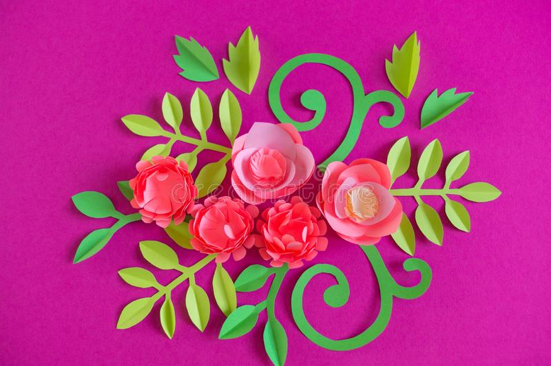 Flower made of paper pink background. Trend color pastel coral. Handwork is a favorite hobby. Florist salon advertising. Green tropical leaf and curl stock photography