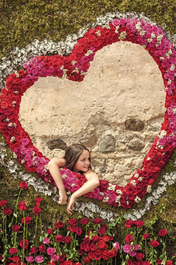 Flower madness. Girl in frame of roses on background of heart. Love royalty free stock photography