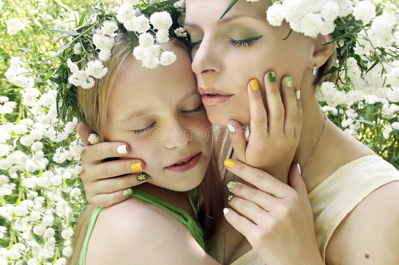 Mother and child are in nature in the summer. Flower manicure with my mother and daughter.Nail art.Mother and child are in nature in the summer in the flower of royalty free stock images