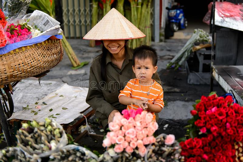 Flower market. HANOI, VIETNAM - SEP 23. 2014: Unidentified woman and her chlld works at the flower market in Hanoi, Vietnam. Flower market in Hanoi is one of the stock photography
