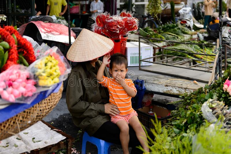 Flower market. HANOI, VIETNAM - SEP 23. 2014: Unidentified woman and her chlld works at the flower market in Hanoi, Vietnam. Flower market in Hanoi is one of the stock photos