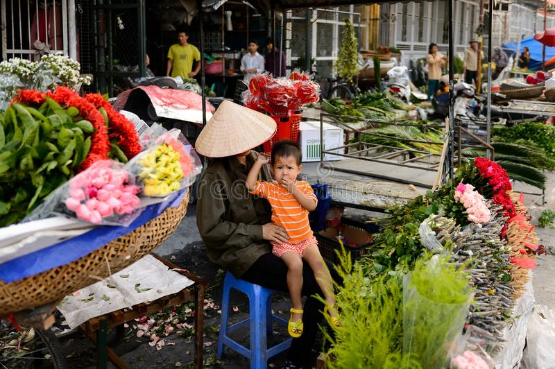 Flower market. HANOI, VIETNAM - SEP 23. 2014: Unidentified woman and her chlld works at the flower market in Hanoi, Vietnam. Flower market in Hanoi is one of the royalty free stock photo