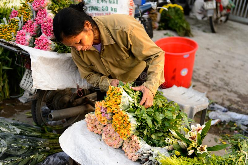 Flower market. HANOI, VIETNAM - SEP 23. 2014: Unidentified woman works at the flower market in Hanoi, Vietnam. Flower market in Hanoi is one of the largest royalty free stock image