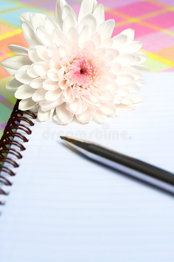Flower with notebook and pen. Closeup of flower with notebook and pen stock image