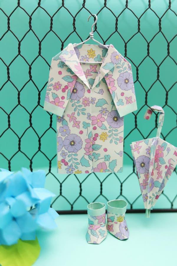 Flower pattern origami rain goods, raincoat, umbrella, boots royalty free stock photography
