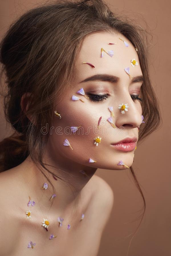 Flower petals on face girl, woman cosmetics to moisturize face skin, reduce wrinkles, clean healthy skin. Flowers on the face and. Body of a woman, anti-wrinkle royalty free stock photos