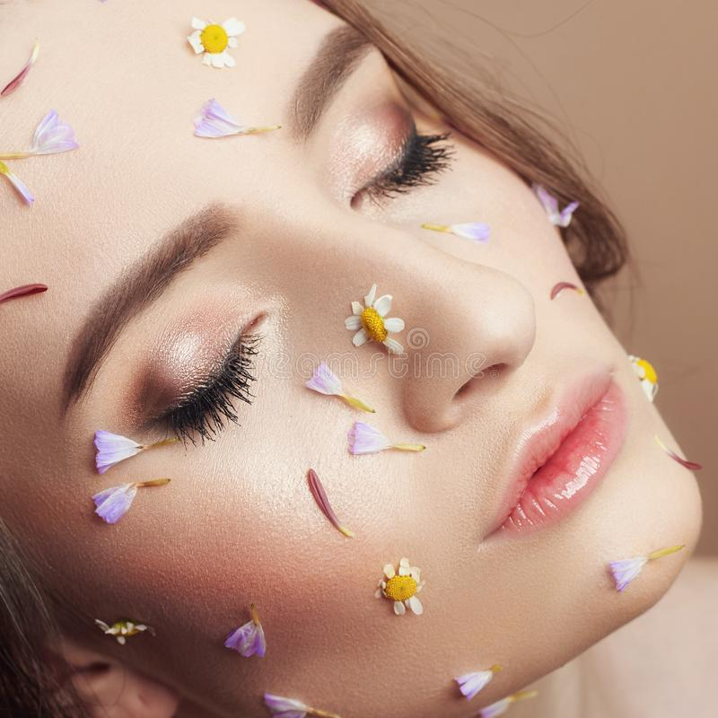 Flower petals on face girl, woman cosmetics to moisturize face skin, reduce wrinkles, clean healthy skin. Flowers on the face and. Body of a woman, anti-wrinkle stock photo