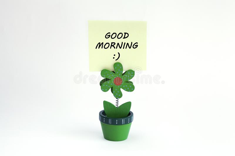 Flower photo clip with good morning message written on post it. Green wood flower photo clip with good morning message wrtitten on post it royalty free stock photography