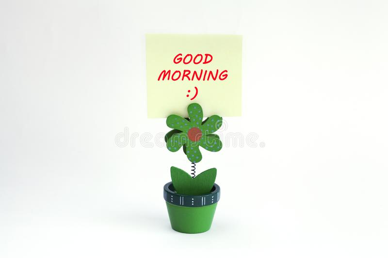Flower photo clip with good morning message written on post it. Green wood flower photo clip with good morning message wrtitten on post it royalty free stock image