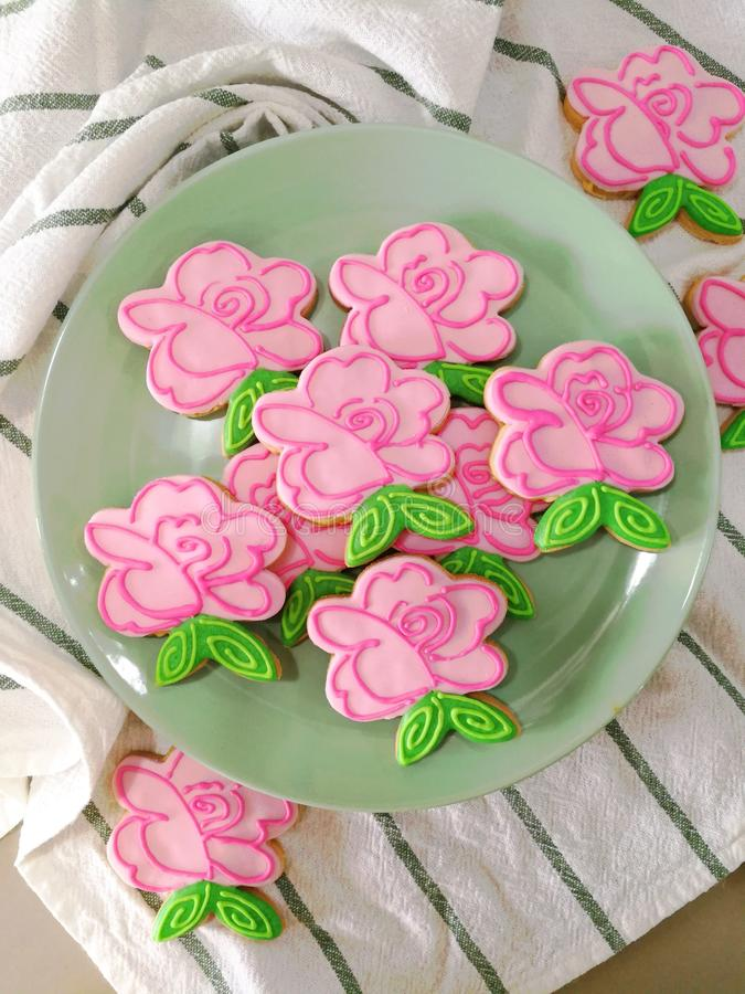 Flower pink rose fancy hand made spring and summer style sugar cookies with royal icing on plate and tablecloth stock photo