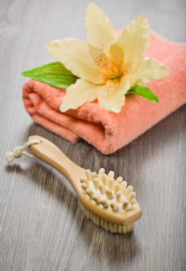 Flower on pink towel with massager and brush stock photo