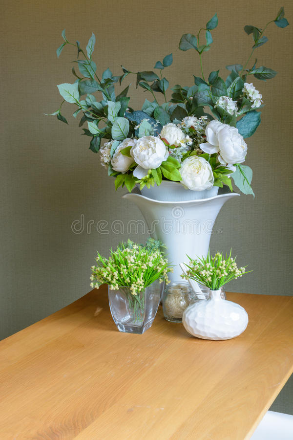Flower and plant in vase. On wooden table stock photography
