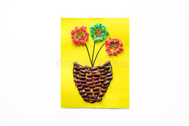 Children`s seasonal crafts from natural materials. Flower in pot from cereals, beans, dried leaves and colored paper Children`s seasonal crafts from natural royalty free stock photography