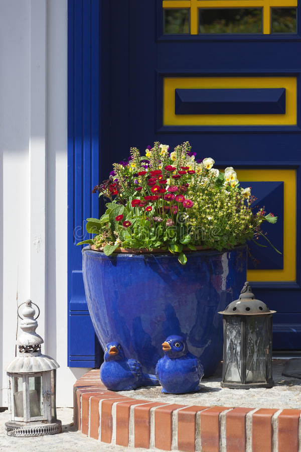 Flower Pot And Decoration In Front Of Blue Door Stock