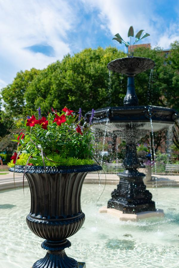 Flower Pot with Flowers in front of a Beautiful Fountain and Garden at a Park in Wicker Park Chicago royalty free stock photography