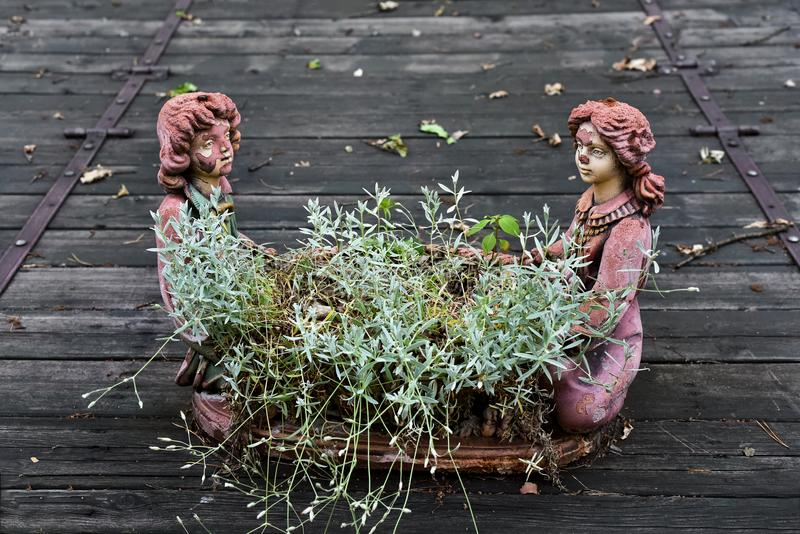 Flower pot in the form of a chelovke boy and girl. Old with cracks green grass stock images