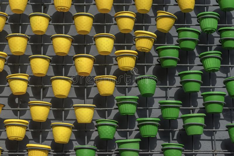 Flower pots of green yellow colors on concrete wall as spring, summer art decor. Modern natural natural graphic. Flower pots of green yellow colors on concrete stock photos