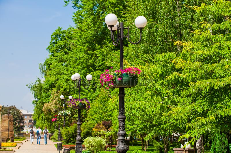 Flower pots on a lampposts in urban public place, Donetsk royalty free stock photography